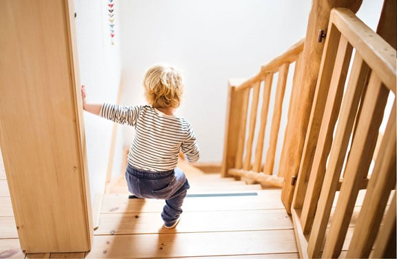 A toddler walking down the stairs where he might suffer an injury due to dangerous premises