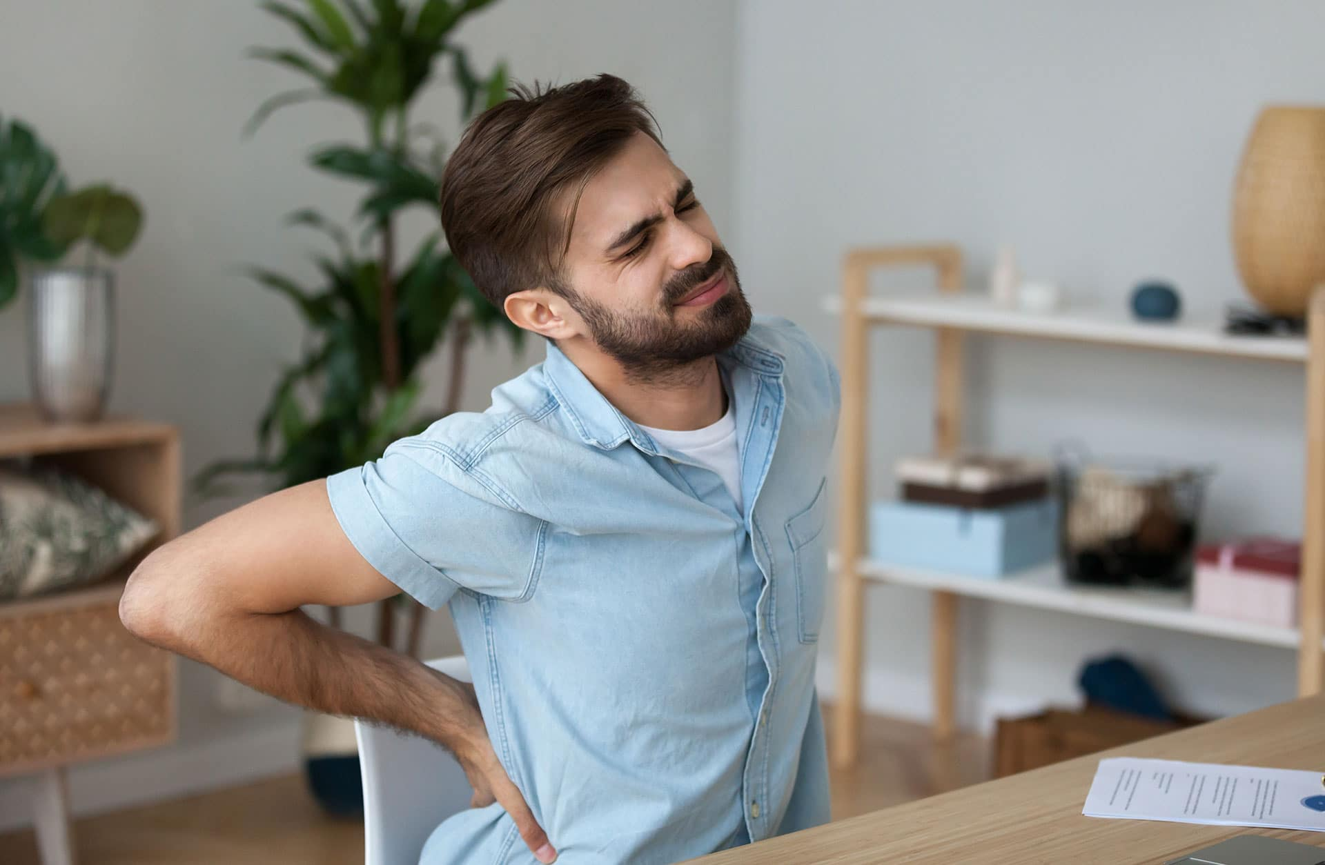 A man holding his back and grimacing in pain after a spinal cord injury