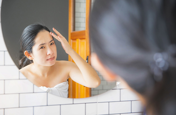 A woman looking at herself in the mirror checking a spot on her forehead.