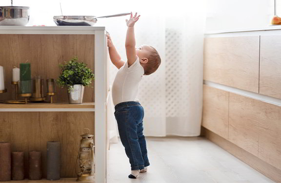 A toddler attempting to reach up and grab a pan that is on a stovetop.